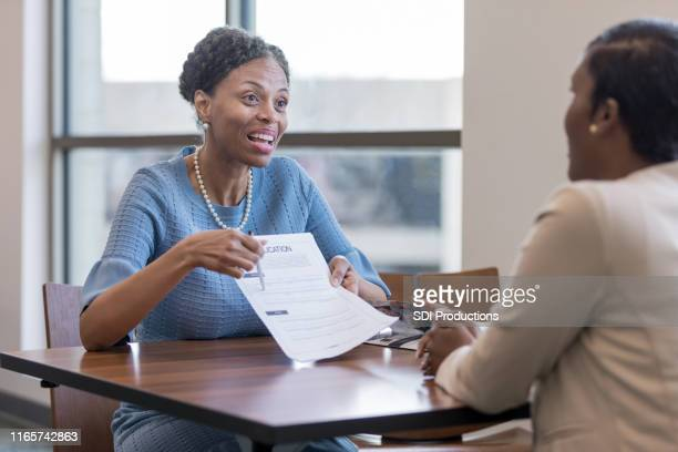 senior female personal banker shows client account application - representing stock pictures, royalty-free photos & images