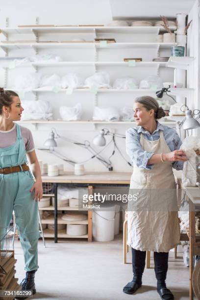 senior female potter working with young employee against shelves at workshop - craft product stock pictures, royalty-free photos & images