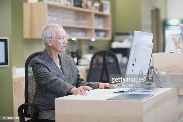 senior female receptionist using desktop computer at hotel reception desk - sigrid gombert stock-fotos und bilder