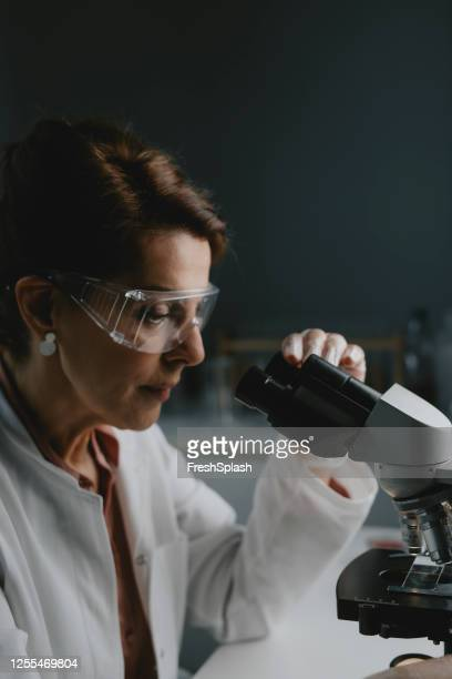 senior female scientist/lab technician doing research by using a microscope - microscope stock pictures, royalty-free photos & images