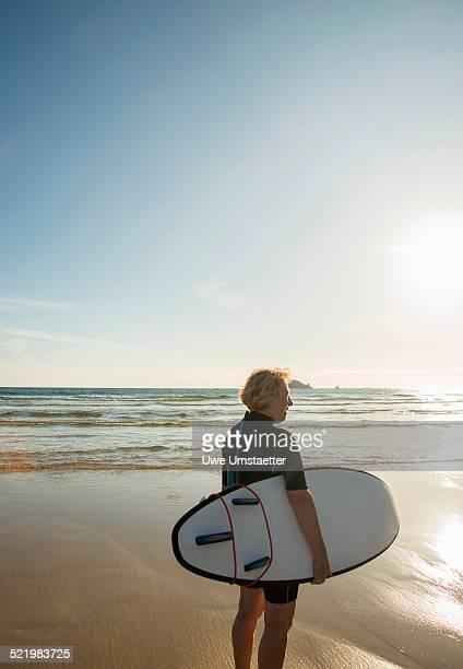senior female surfer standing on beach with surfboard, camaret-sur-mer, brittany, france - camaret sur mer photos et images de collection