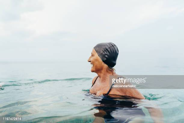 senior female swimmer in the sea - hobbies stock pictures, royalty-free photos & images