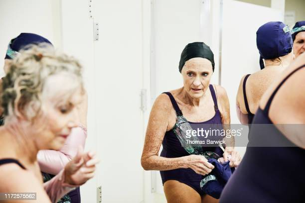 Senior female synchronized swim team getting ready for show in locker room