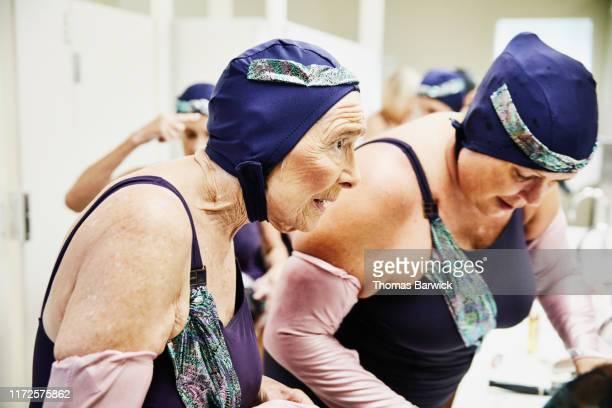 Senior female synchronized swimmer preparing for show in locker room with teammates