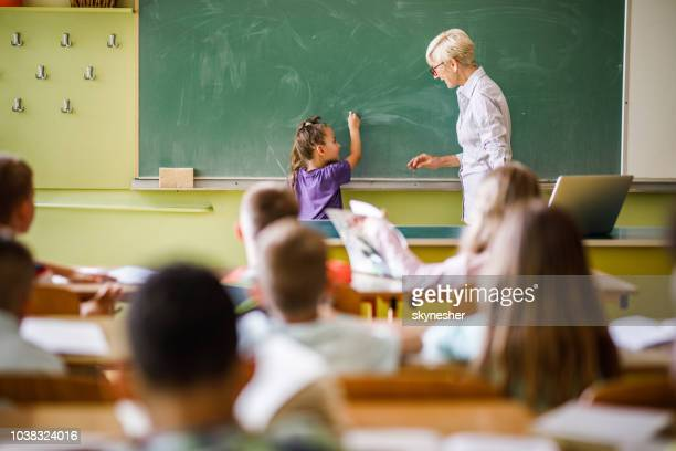senior female teacher teaching schoolgirl in front of blackboard at elementary school. - lecture hall stock pictures, royalty-free photos & images