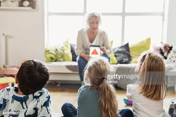 Senior female teacher teaching students in day care center