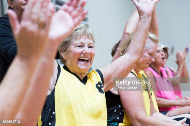 senior female team player celebrating with arms in the air