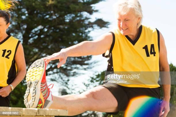 Senior female team player stretching outdoors