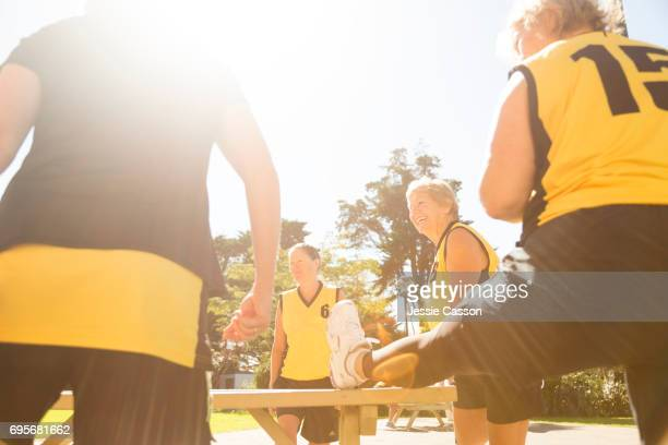senior female team players stretching outdoors - leanincollection stock pictures, royalty-free photos & images