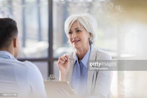 senior female therapist gives advice to male patient - psychologist stock photos and pictures