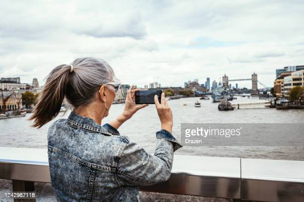 senior female tourist in london taking photos with smart phone - northern european descent stock pictures, royalty-free photos & images