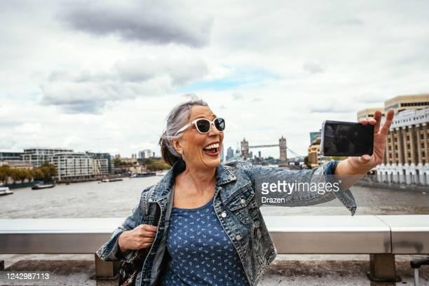 senior touristin in großbritannien fotografiert mit smartphone mit tower bridge im hintergrund - central london stock-fotos und bilder