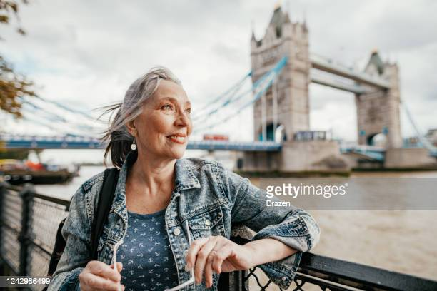 senior female tourist with blue eyes in london near tower bridge, traveling to uk after pandemic - northern european descent stock pictures, royalty-free photos & images
