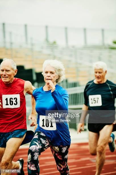 senior female track athlete leading distance race with men on track - sporting term stockfoto's en -beelden