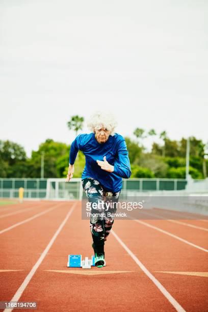Senior female track athlete starting sprint out of starting blocks on track