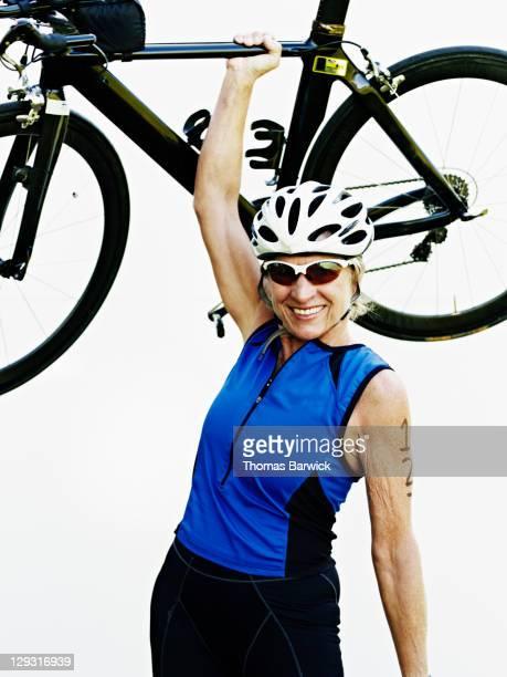 Senior female triathlete holding bike over head