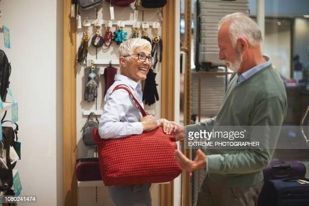 senior femelle tente sur un sac de messager rouge et montrer à son partenaire dans un magasin de sacs à main - crossbody bag photos et images de collection
