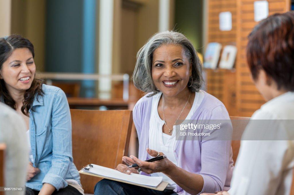 Senior female university professor teaches in casual setting : Stock Photo