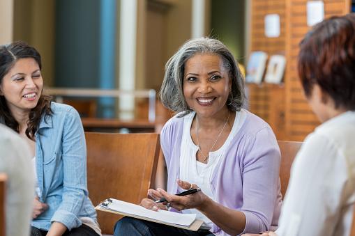 Senior female university professor teaches in casual setting 956725740