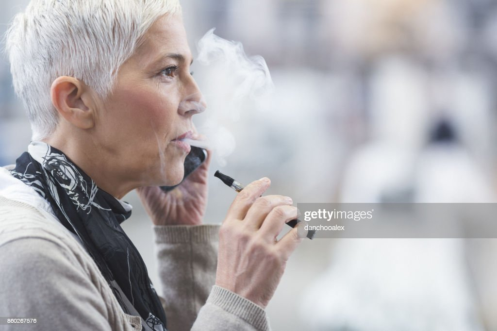 Senior female using electronic cigarette : Stock Photo