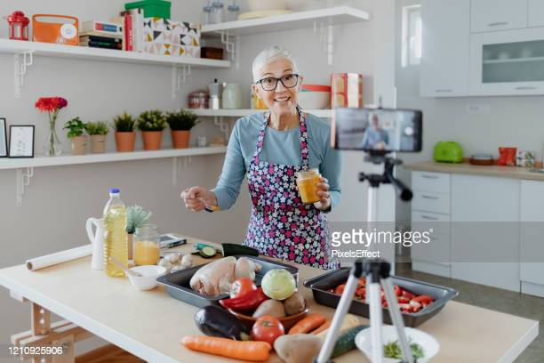 senior female vlogger making social media video about cooking - course meal stock pictures, royalty-free photos & images
