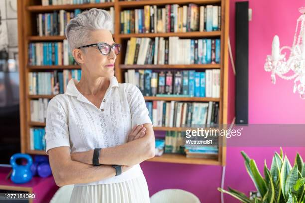 senior female with arms crossed standing against bookshelf at home - one senior woman only stock pictures, royalty-free photos & images