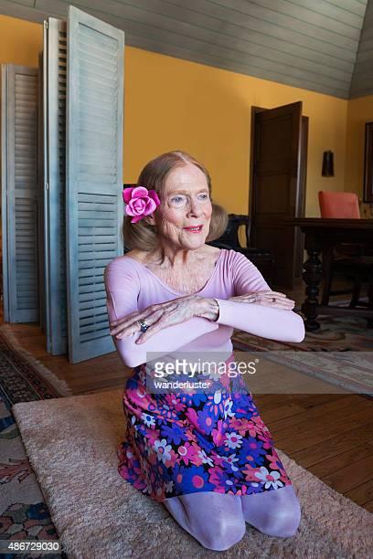 Senior femme professeur de yoga qui s'étend à la maison