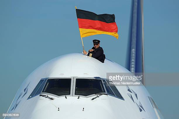 Senior first officer Andreas Rickart waves the german flag during the arrival of German Summer Olympic Athletes from the Olympic Games in Rio at...