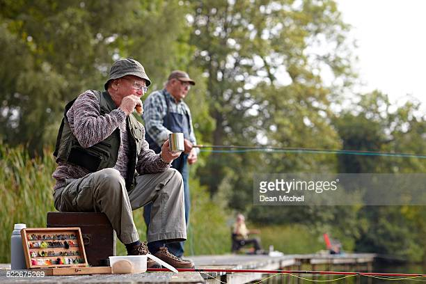 senior fisherman having lunch - fishing tackle stock pictures, royalty-free photos & images