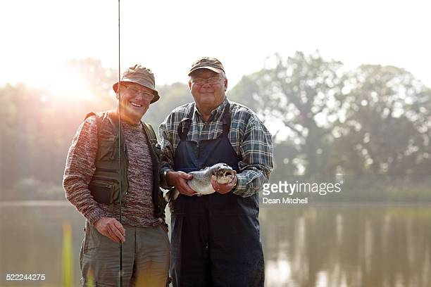 senior fishermen with rod and fresh catch - big fish stock pictures, royalty-free photos & images
