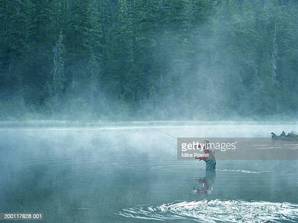 Senior fly fisherman standing in lake covered with fog, casting line