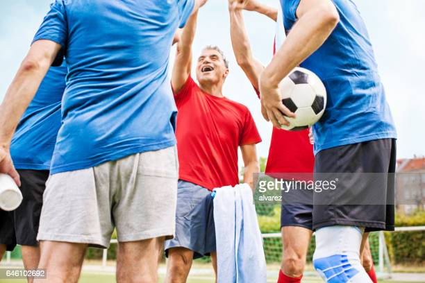 senior football players cheering - calcio di squadra foto e immagini stock