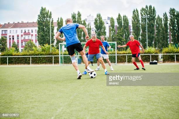 jogadores de futebol sênior em ação - defesa jogador de futebol - fotografias e filmes do acervo