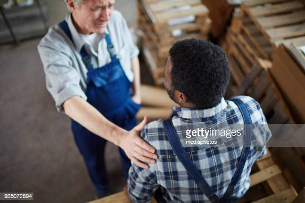 senior foreman of plant supporting young employee - hand on shoulder stock pictures, royalty-free photos & images