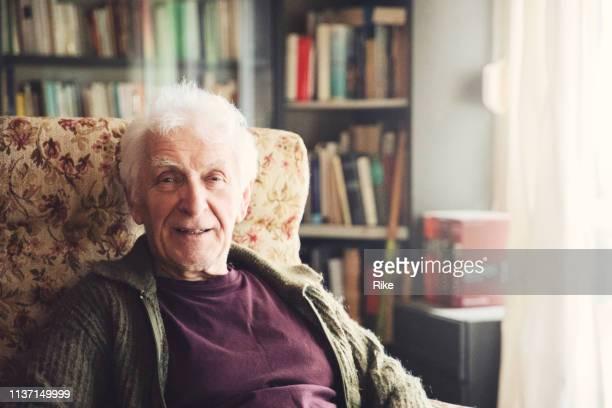 senior freundliche herren sitzt in seinem stuhl - nordeuropäischer abstammung stock-fotos und bilder