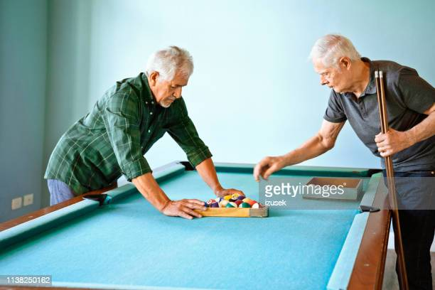 senior friends arranging balls on pool table - old men playing pool stock pictures, royalty-free photos & images