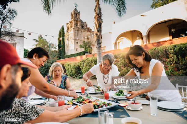 senior friends at garden party reunion - mexican food stock pictures, royalty-free photos & images