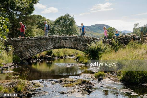 senior friends crossing stone bridge. - small group of people stock pictures, royalty-free photos & images