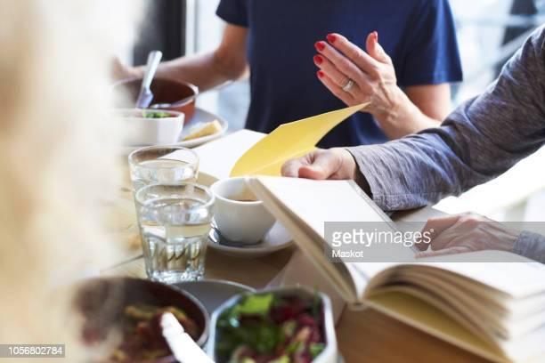 Senior friends enjoying food in book club at restaurant
