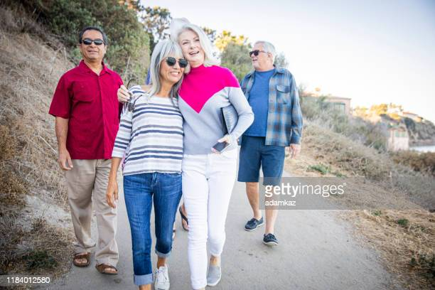 amis aînés allant à la plage - medicare photos et images de collection