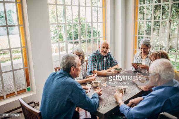 amigos seniores se divertindo jogando cartas - carta de baralho jogo de lazer - fotografias e filmes do acervo