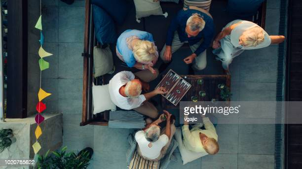 senior friends playing backgammon - board game stock pictures, royalty-free photos & images