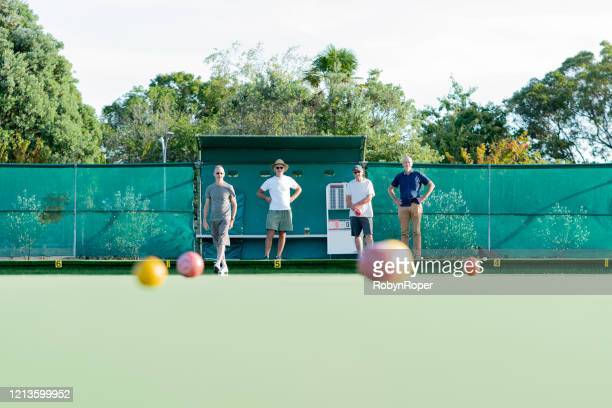 Senior friends playing social lawn bowls outdoors