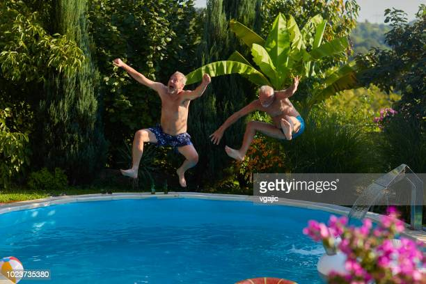 senior friends pool fun - young at heart stock pictures, royalty-free photos & images