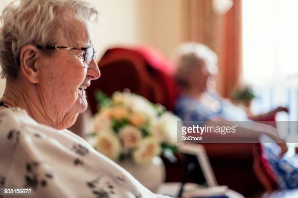 senior friends sitting in a nursing home - fragility stock pictures, royalty-free photos & images