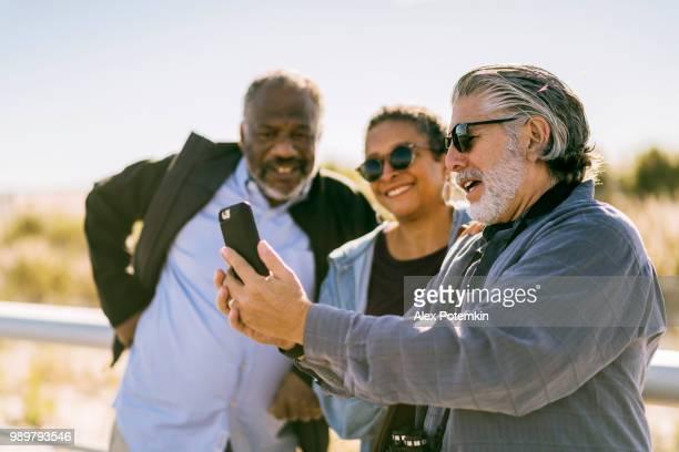 Senior friends take selfie at the beach