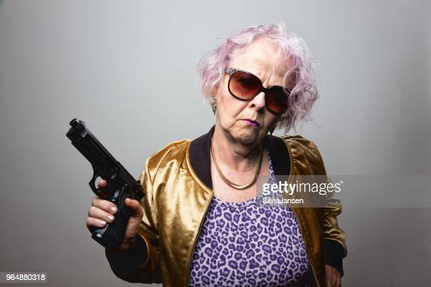 senior gangster lady holding gun
