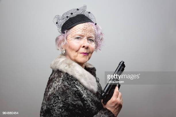 senior gangster lady holding gun - weapon stock pictures, royalty-free photos & images