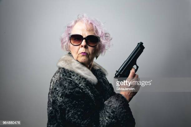 senior gangster lady holding gun - gangster stock pictures, royalty-free photos & images