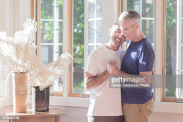 senior gay couple affectionately holding each other and slow dancing in living room - gay seniors photos et images de collection